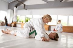 Boy sitting on girl after winning aikido fight with her royalty free stock photo