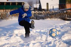 Schoolboy boy kicks the ball playing in winter football on the s. A boy in winter clothes playing football on the snow. Football player kicks the ball.The Royalty Free Stock Photography
