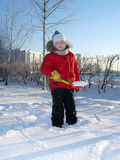 A boy in winter clothes playing with snow. royalty free stock photography