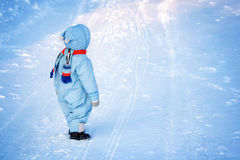 Boy in winter clothes at snowfall Royalty Free Stock Image