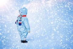 Boy in winter clothes at snowfall Royalty Free Stock Photo