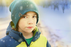 Boy in winter clothes walking in snow city park Stock Image
