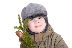 Boy in winter coat with a branch of fur tree Royalty Free Stock Images