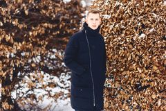 Boy in a winter jacket among the winter trees. Boy in a winter jacket among the trees in winter Stock Photos