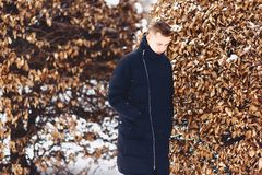 Boy in a winter jacket among the winter trees. Boy in a winter jacket among the trees in winter Stock Images