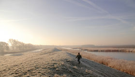 Boy in Winter Landscape. Small boy walking alone in a winter landscape of a dike and two canals Stock Photos