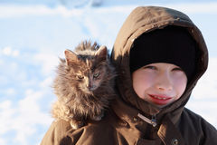 Boy at winter outdoors, cat sits on shoulder Royalty Free Stock Photos