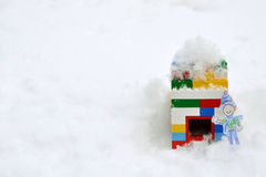 Boy in winter snow waving outside block house Stock Photo