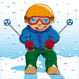 Boy in winter suit rides on the ski hill Stock Images