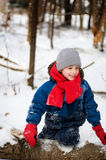 Boy in winter wear outdoors. Six year old boy wearing a hat, a red scarf and red mittens while playing outdoors in winter Royalty Free Stock Photos
