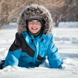 Boy in winterwear laughing while playing in snowdrift outside Royalty Free Stock Photo