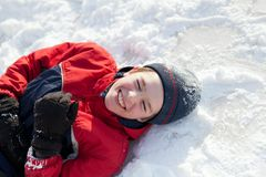Boy in winterwear laughing while playing in snowdrift outside Royalty Free Stock Image