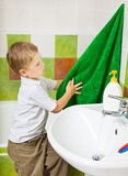 Boy wipes hands a terry towel after washing. Personal hygiene. The boy wipes hands a terry towel after washing Royalty Free Stock Images