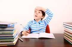 Boy wipes his forehead with his hand. Boy sitting at a desk, writing in pencil in a notebook and wipes his forehead with his hand.boy 5 years. on the desk a lot Stock Photos