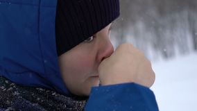 Boy wipes his nose in the cold in winter. Footage the boy wipes his nose in the cold in winter. Slow motion 120fps stock video footage