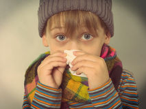 Boy wiping his nose Stock Photography
