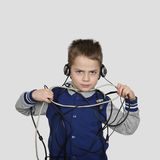 Boy in wires. Serious little boy in headphones tangled in cables and trying to remove them from himself on gray background - Wire and wireless communication Royalty Free Stock Images