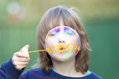 Boy With Blond Hair Blowing Bubbles Stock Photo