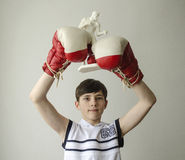 Free Boy With His Hands Raised In Boxing Gloves In A Victory Gesture With A Figurine Of A Boxer Royalty Free Stock Photography - 85615737