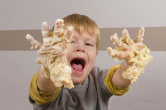 Boy With Sticky Hands Full Of Dough Royalty Free Stock Photography