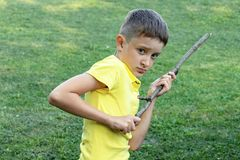 A boy witn angry face holding a stick in his hands.  stock photos