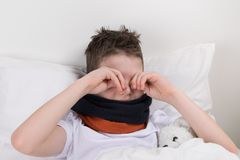 The boy woke up in bed, does not want to stand up rubs his eyes, his throat hurts Stock Images
