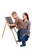 A boy, woman and blackboard.Writing. The boy begins to write on the blackboard. He wants to draw or write something. The women is watching what he does stock photos