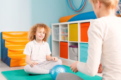 Boy and woman playing with a ball. Smiling boy and a women playing with a ball during sensory integration session Royalty Free Stock Photos
