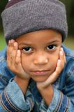 Boy Wondering. Boy sitting and wondering with his face in his hands Stock Photo