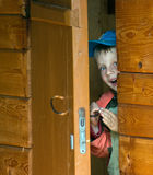 Boy in a wooden house. The child looks through slightly opened wooden a door Royalty Free Stock Photography