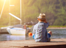 Boy on wooden pier looking for a yahts Royalty Free Stock Photo