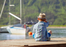Boy on wooden pier watching the yachts Royalty Free Stock Image