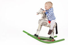 Boy and wooden rocking horse. Blond boy riding wooden rocking horse Royalty Free Stock Images