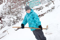 Boy with a wooden shovel for snow removal Royalty Free Stock Photo
