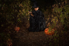 Boy in the woods, dressed as a magician with Halloween pumpkin Jack Royalty Free Stock Photography