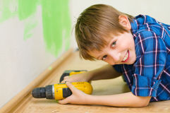 Boy worker installing plinth. Little boy worker installing plinth at home stock images
