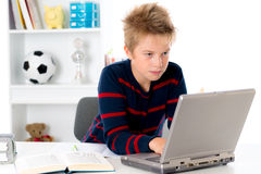 Boy is working with book and computer Royalty Free Stock Photography
