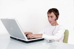 Boy working on computer. Young teenage boy sitting at a desk with a headset working on a notebook computer Royalty Free Stock Images