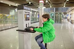 A boy is working at computer in airport stock photo