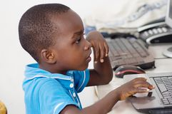 Boy working on a computer. This child is focused on his work at the computer Royalty Free Stock Photography