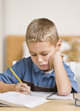 Boy Working on Homework. A young boy is working on his homework at the table.  He is looking down at what he is doing.  Vertically framed shot Royalty Free Stock Photography