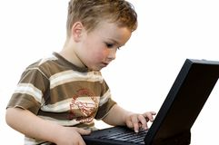 Boy working on a laptop. Five year old boy working on a laptop computer royalty free stock photography