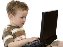 Boy working on a laptop. Five year old boy working on a laptop computer stock image