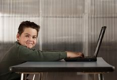 Boy working on a laptop computer Stock Photo