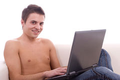 Boy working with laptop on couch Royalty Free Stock Photos