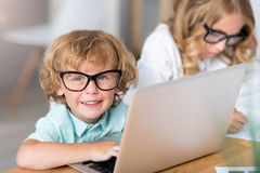 Boy working on laptop and looking strait Royalty Free Stock Image