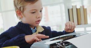 Boy working on typewriter in the office 4K 4k. Close-up of boy working on typewriter in the office 4K 4k stock footage