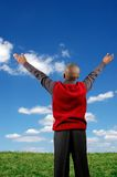 Boy Worshipping. Boy with arms raised expressing joy over a blue sky with clouds Royalty Free Stock Photo