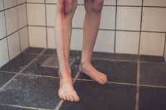 Boy with Wounded Knee Takes Shower in the Bathroom. Wounded Knee of a Boy with Blood Running Down onto the Floor, Taking Shower in the Bathroom Stock Photo