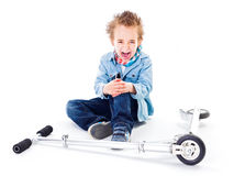 Boy with wounded leg near by scooter Stock Images